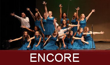 Mainstage's Encore Show Choir clumped together in an ending pose with their right arms outstretched.
